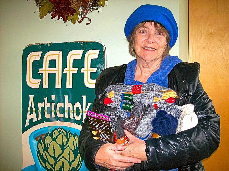RITA A. LEONARD - Alexa MacDonald of Artichoke Music holds some of the wool sock pairs recently collected for the homeless at one of their concerts.