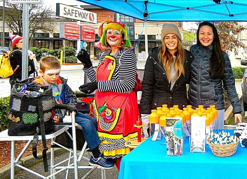 ELIZABETH USSHER GROFF - Outside Woodstock Safeway, OnPoint Credit Union celebrated its grand opening on December 16th, including face painting by Bizzy the Clown - here applying paint to the face of 7-year-old Sam, son of Brie Kruger, who is a Woodstock OnPoint member.