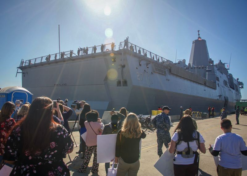 U.S. NAVY PHOTO BY MASS COMMUNICATION SPECIALIST 2ND CLASS JESSE MONFORD - Local media and families gather on the pier as the future San Antonio-class amphibious transport dock ship USS Portland (LPD 27) arrives into its new homeport of San Diego. It is scheduled to be ceremoniously commissioned Apr. 21 in Portland.