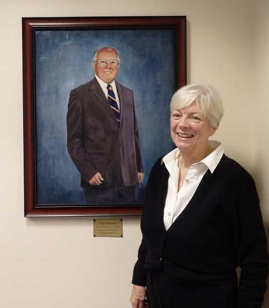 Peggy Peterson stands beside the commemorative portrait of her husband, Don. The painting now hangs in the Don Peterson Boardroom at DirectLink.