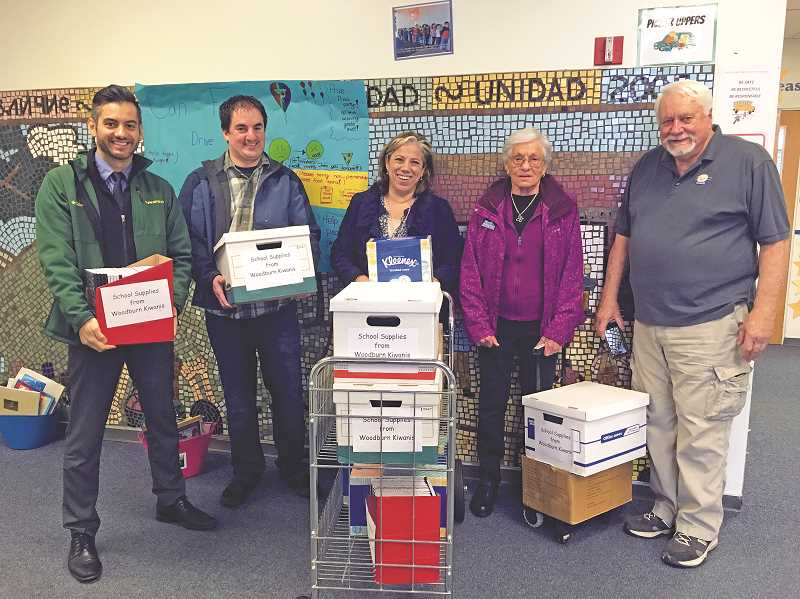 LINDSAY KEEFER - Washington Principal Alfredo Belanger (left) and Vice-Principal Claudia Kis (center) pose with Kiwanians (from left) Michael Nelson, Nancy Kirksey and Walt Mangerich during Thursday's delivery to the school.