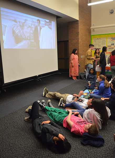TIDINGS PHOTO: VERN UYETAKE  - Students get comfortable and watch the movie.