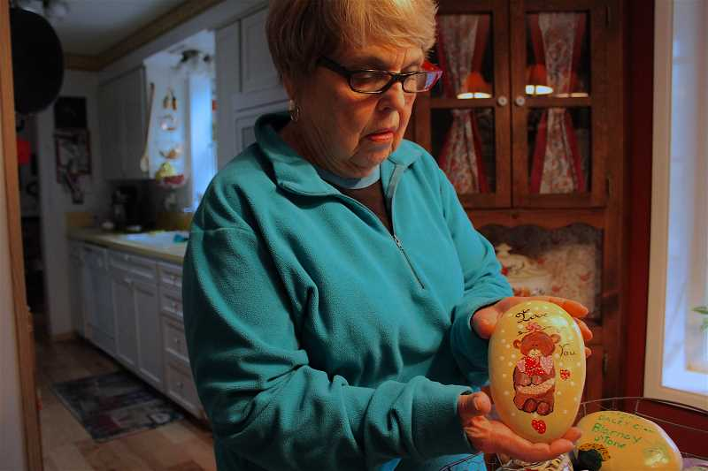 REVIEW PHOTO: SAM STITES - Kay Simons holds a rock emblazoned with a Valentines Day teddy bear.
