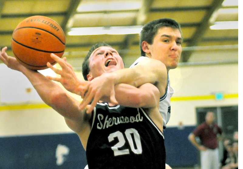 SETH GORDON - Senior Garrett Myers fouls Sherwood's Owen Grubbe on a fast break during Newberg's 64-45 home loss Jan. 17. The Tigers rebounded to beat Lakeridge 63-59 Friday night.