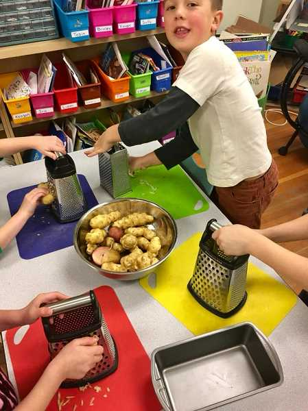 COURTESY PHOTO - Community school students have frequent opportunities for hands-on activities, like making their own potato pancakes.