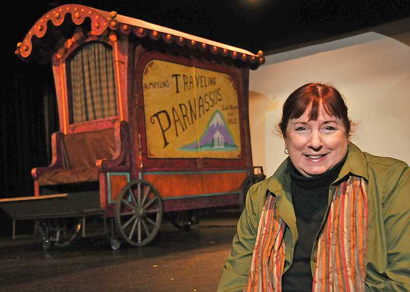 PAMPLIN MEDIA GROUP PHOTO: VERN UYETAKE  - Playwright C.S. Whitcomb sits next to the book wagon used in her play Parnassus on Wheels, currently being presented by Lakewood Theatre Company at Lakewood Center for the Arts.