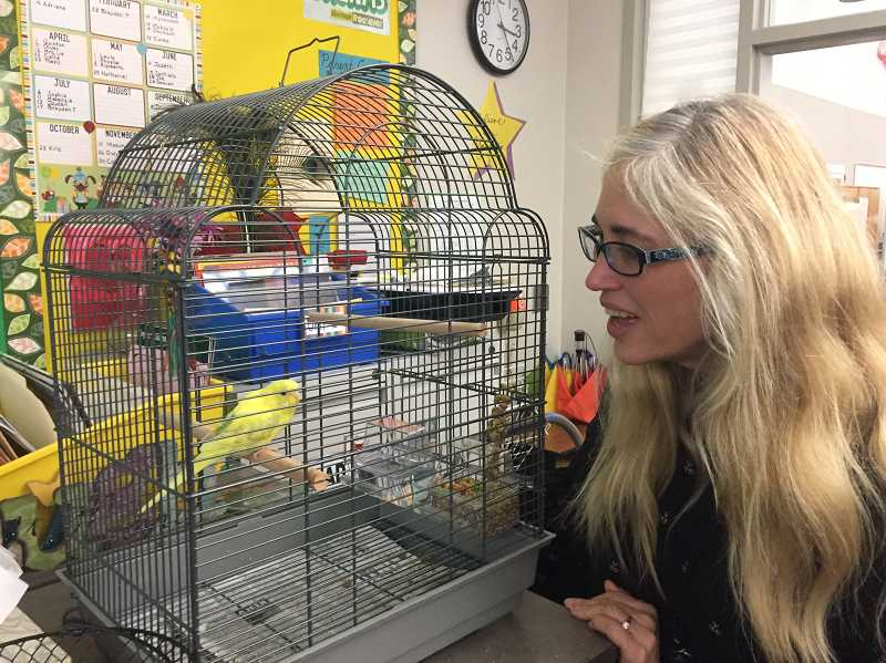 ESTACADA NEWS PHOTO: EMILY LINDSTRAND - Joan Lawrence smiles at the bird who lives in her classroom. Lawrence has taught at the Estacada School District for 31 years.