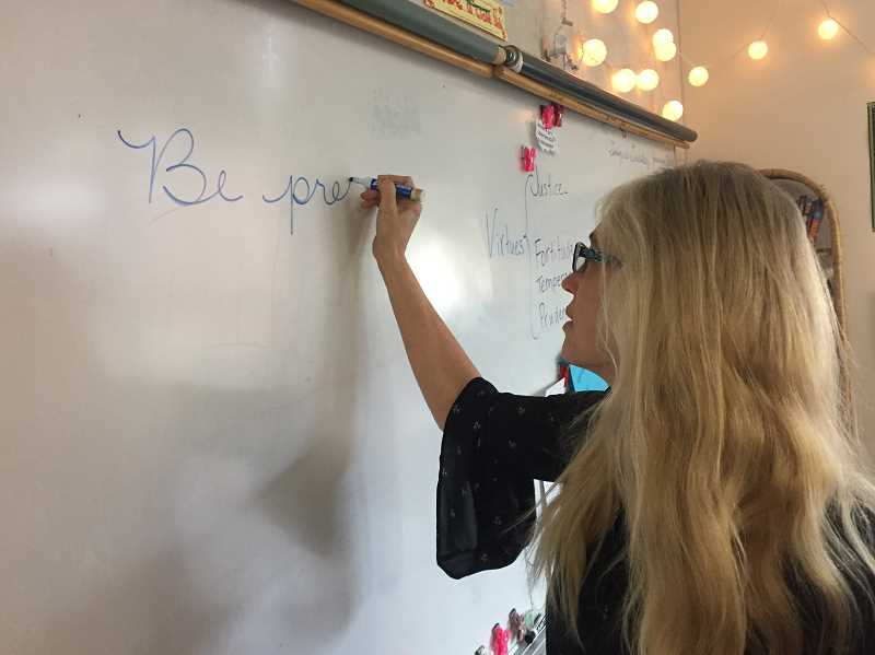 ESTACADA NEWS PHOTO: EMILY LINDSTRAND - Joan Lawrence writes on the whiteboard in her classroom at Clackamas River Elementary School.