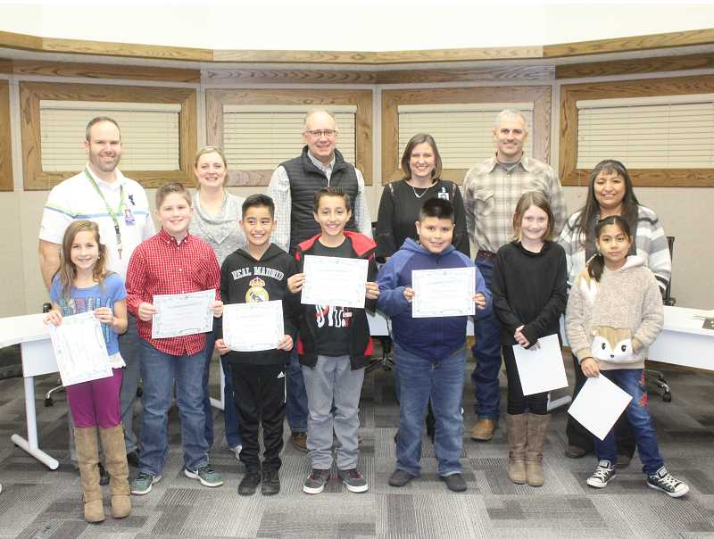 SUSAN MATHENY/MADRAS PIONEER - Awarded at Monday's school board meeting were Madras Primary students, left to right, Cara Todd, Joshua Gregory, Fernando Saldaña, Isaiah Rubio Moschetti, Israel Reynoso Ortega, Anaiah Demoran, and Jessica Arzate Rosales. (Not pictured, Edward Robinson, Grace Fang and Aspen Toman.) Honoring them, from back left are, teacher Steele Bailey, board members Courtney Snead and Stan Sullivan, Madras Elementary Principal Deborah Hunt, board member Tom Norton Jr., and board Chairman Laurie Danzuka.