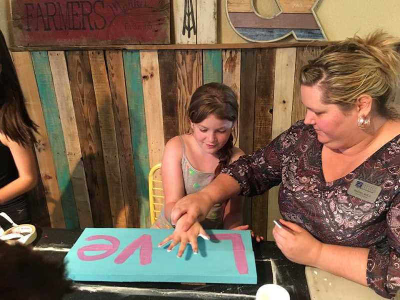 SUBMITTED PHOTO - A 'Big' helps helps her 'Little' during a Big Brothers Big Sisters art project.