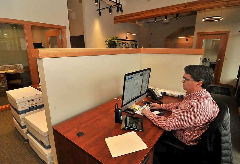 STAFF PHOTOS: VERN UYETAKE  - Harnish Properties agent Chris Grubb works in the companys new offices located on B Avenue in Lake Oswego.