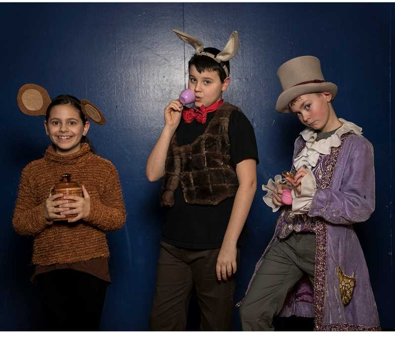 SUBMITTED PHOTO: TOM HAUCK - Lake Grove fifth-graders Lili Grimm as the Dormouse, Roark Smith as the March Hare and Owen Benincosa as the Mad Hatter pose before performing in 'Alice (Inside Out) in Wonderland.'