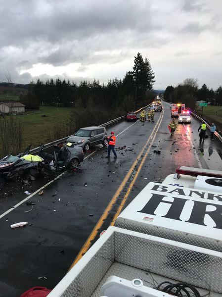 COURTESY OF THE BANKS FIRE DISTRICT - A photograph of the scene of the crash on Highway 6 near Aerts Road shows multiple damaged vehicles and debris scattered across both lanes of travel.
