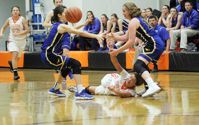 WILL DENNER/MADRAS PIONEER - Irma Retano (middle) flings a pass from the ground to Mikayla Haessler, who proceeded to score an unconstested layup late in the fourth quarter.