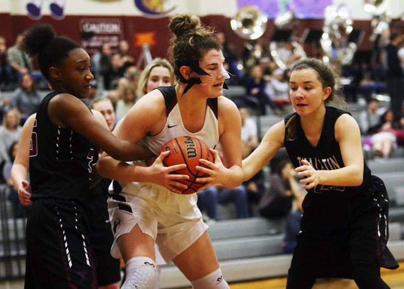DAN BROOD - Sherwood junior Kaytlin Cooke (center) battles to keep the ball from Tualatin's Maliya Ross (left) and Mikah Springer during Tuesday's game.