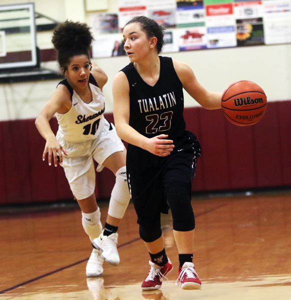DAN BROOD - Tualatin senior Mikah Springer (right) looks to move the ball up court ahead of Sherwood freshman Kylah Williams.