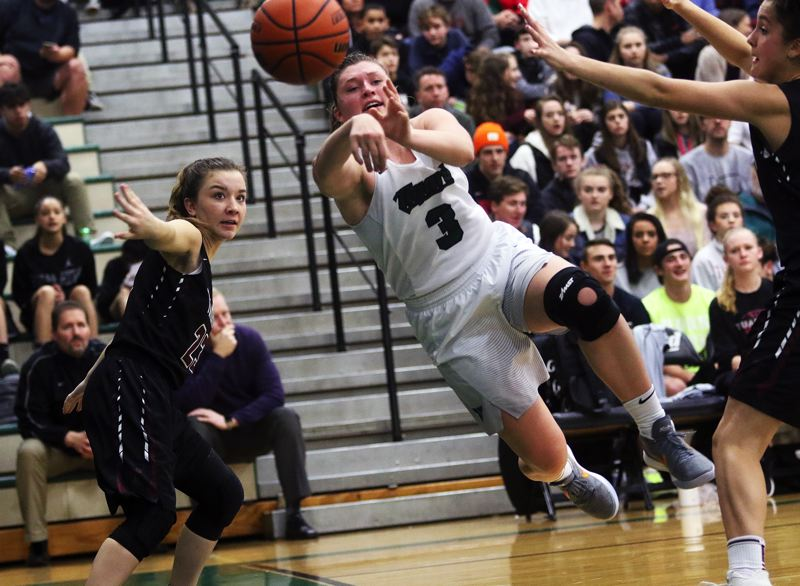 DAN BROOD - Tigard High School junior guard Campbell Gray throws a pass past Tualatin senior Mikah Springer during last week's contest.