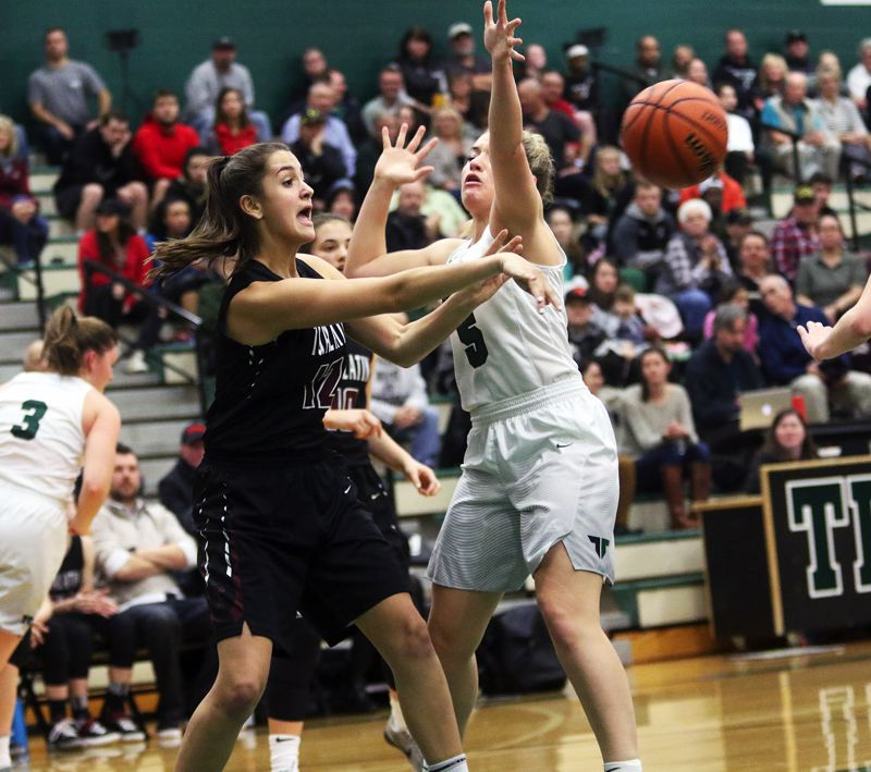 DAN BROOD - Tualatin freshman Sidney Dering throws a pass past Tigard senior Gabby McGaughey.