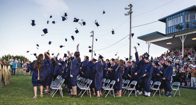 FILE - In a 2016 photo, Banks High School graduates throw their caps into the air.