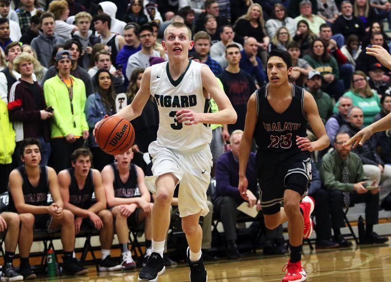 DAN BROOD - Tigard High School junior point guard Jake Bullard, in front of Tualatin senior Alexis Angeles, looks to drive to the basket during last week's game. The Tigers came away with a 65-62 victory.