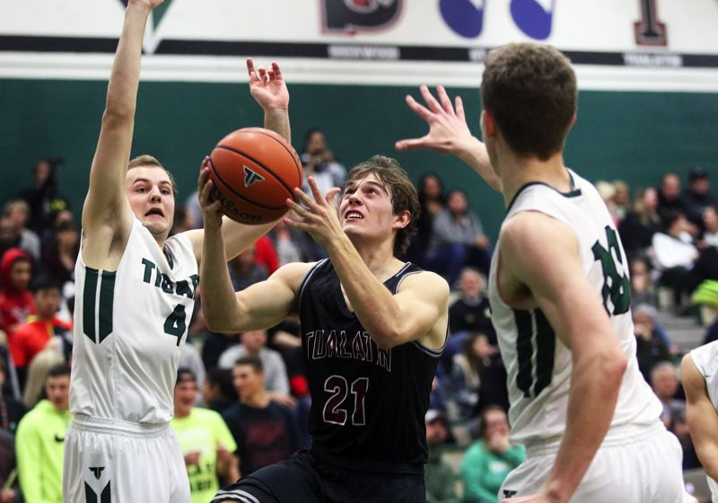 DAN BROOD - Tualatin senior Lucas Noland (21) looks to get to the basket between Tigard's Stevie Schlabach (left) and Austin Dufort.