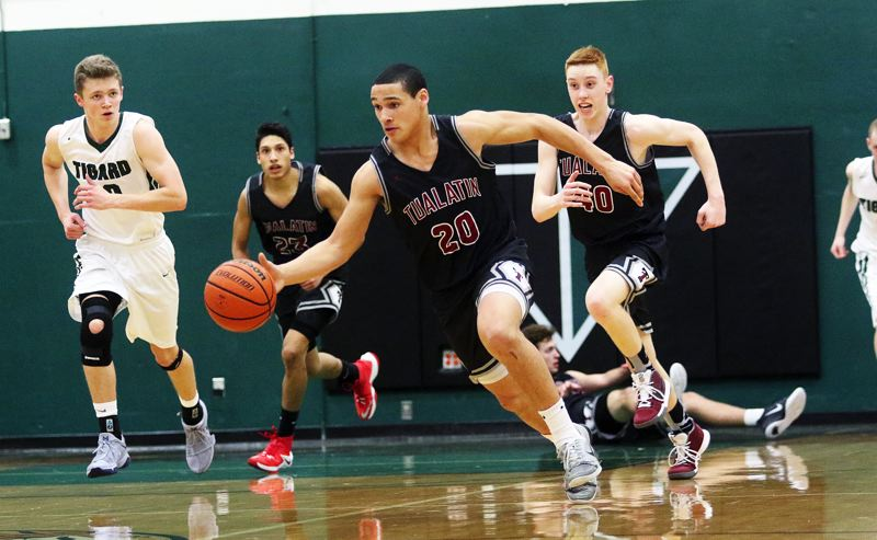 DAN BROOD - Tualatin sophomore John Miller leads a fast break during the game at Tigard.