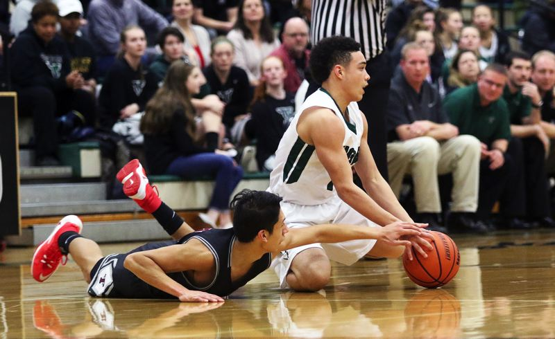DAN BROOD - Tualatin senior Alexis Angeles (left) and Tigard sophomore Max Lenzy battle for the ball.