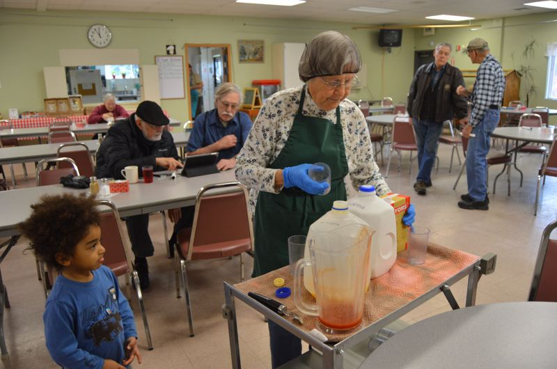 SPOTLIGHT PHOTO: COURTNEY VAUGHN - Kathy Meyers, a volunteer at the Scappoose Senior Center, pours juice and other beverages during the lunch hour at the senior center. To her left, Felix, 3, watches and waits for juice. The senior center announced recently that it will end the lunch program.