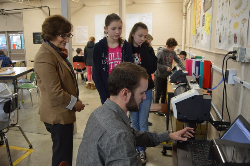SPOTLIGHT PHOTO: NICOLE THILL - Scappoose Middle School science teacher Cameron Boaz, front center, shows U.S. Rep. Suzanne Bonamici how students use a computer aided design program to create designs that are printed in vinyl and turned into custom stickers. The design and modeling class Boaz leads is introduces students to technology concepts at a young age, before other programs are made available to them at the high school level.