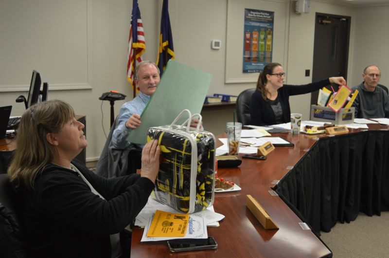 SPOTLIGHT PHOTO: NICOLE THILL - Members of the St. Helens School District school board accept a variety of thank you gifts. Pictured are school board members Melody Killens, Jeff Howell and Bill Amos. Not pictures is Trinity Monahan.