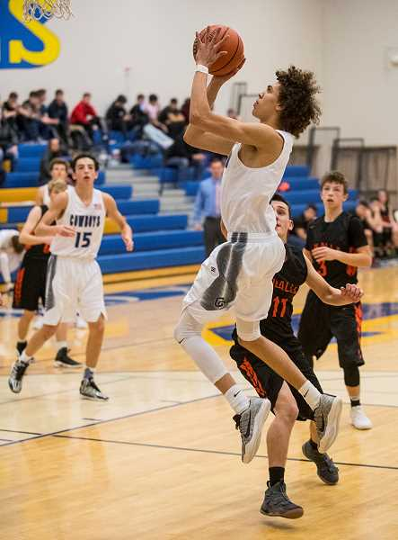 LON AUSTIN/CENTRAL OREGONIAN - Thaiden Mullan goes to the basket for two of his 11 points against Molalla on Tuesday. Mullan, who was in foul trouble most of the night scored nine points in the fourth quarter to help seal the Cowboy 51-42 victory.