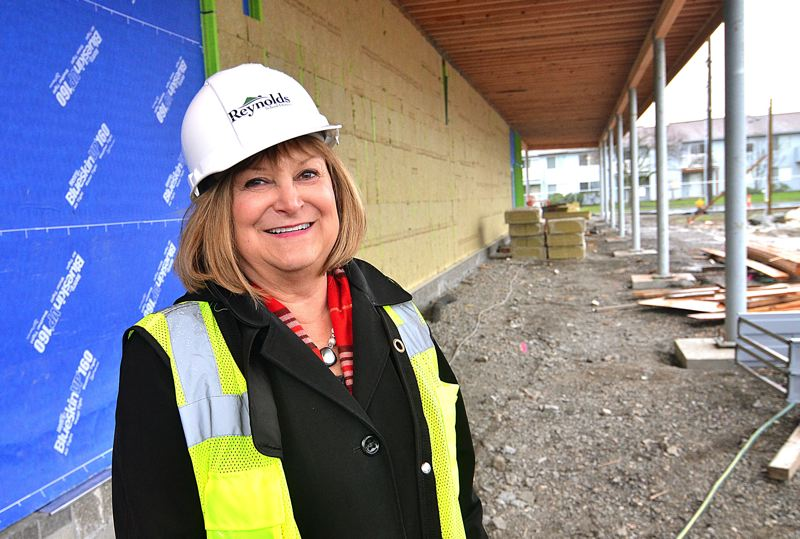 OUTLOOK PHOTO: VERN UYETAKE - Reynolds Superintendent Linda Florence stands near the main entrance to the new Wilkes school. Students will walk down the covered walk to enter the building.