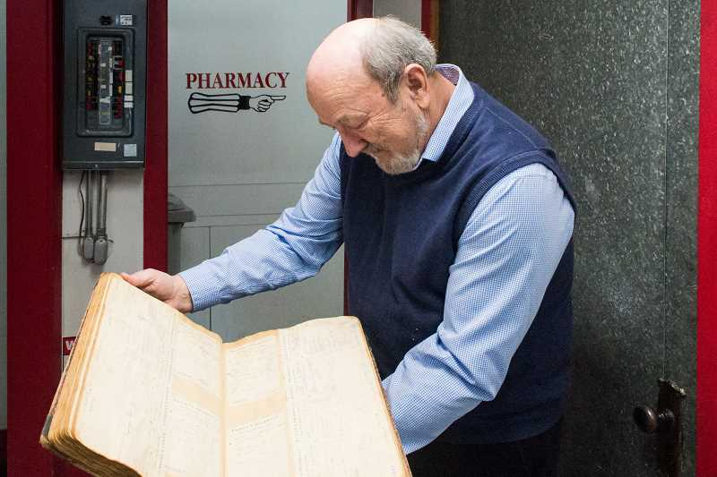STAFF PHOTO: CHRISTOPHER OERTELL - Pharmacy owner Doug Johnson shows a ledger of saved prescriptions going back to 1904 at the Hillsboro Pharmacy and Fountain.