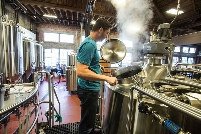 PAMPLIN MEDIA GROUP: FILE PHOTO - Commons Brewery owner Mike Wright checks on the next batch of beer at the brewery's Southeast Portland location.