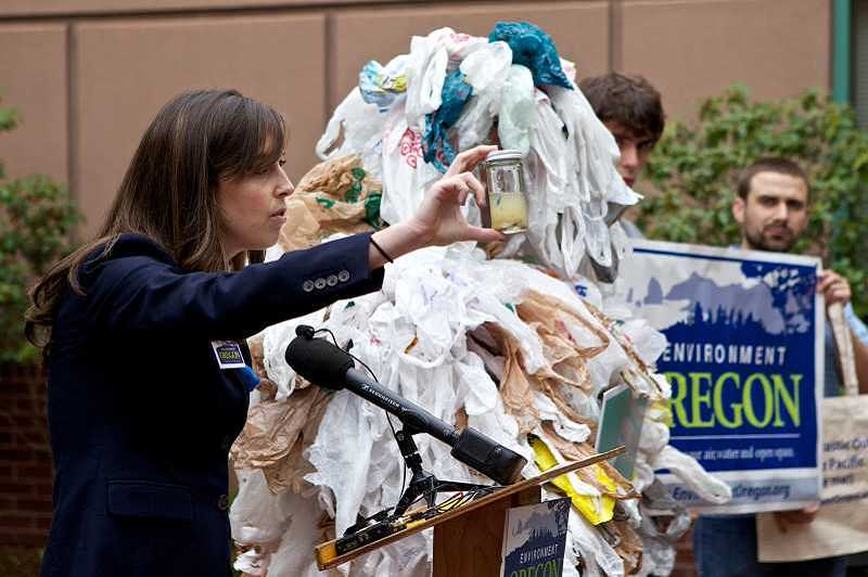 "PAMPLIN MEDIA GROUP FILE PHOTO - Sarah Higginbotham, state director for Environment Oregon, holds up a glass jar of ""toxic soup,"" a collection of trash particles found in the ocean due to the misuse of plastic bags."