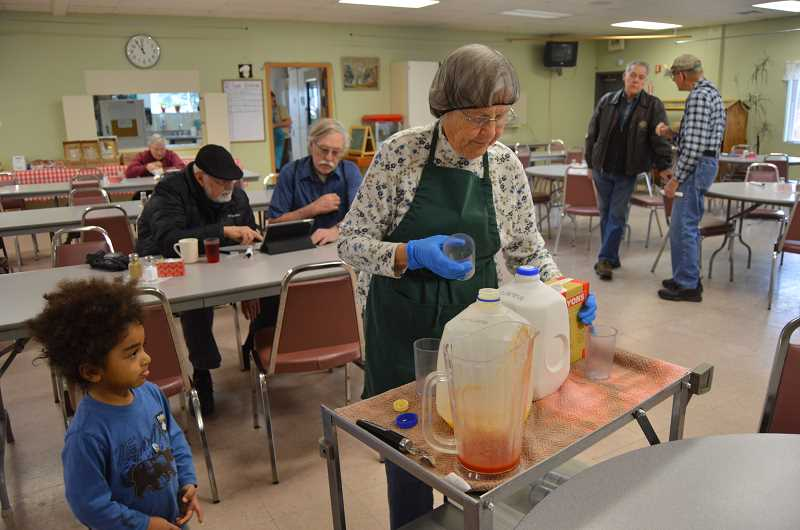 SPOTLIGHT PHOTO: COURTNEY VAUGHN - Kathy Meyers, a volunteer at the Scappoose Senior Center, pours juice and other beverages during the lunch hour at the senior center. To her left, Felix, 3, watches and waits for juice. The senior center announced recently it will end its lunch program.