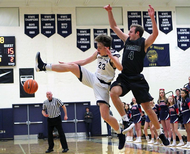 REVIEW PHOTO: MILES VANCE - Lake Oswego's Josh Angle (left) knocks the ball away from Tigard's Stevie Schlabach during the Lakers' 64-42 home win on Friday.
