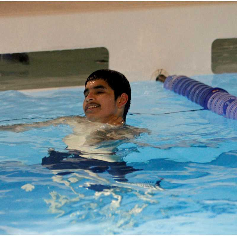 HILLSBORO TRIBUNE PHOTO: WADE EVANSON - Hilhi's Eric Gongora rests between laps during a practice at the Hillsboro Aquatic Center. The tappers the pool uses are attached to the lane line and warns Eric the wall is near.