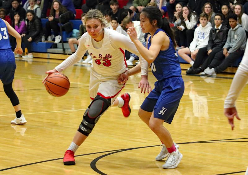 REVIEW/NEWS PHOTO: JIM BESEDA - La Salle Prep's Addison Wedin drives against Hillsboro's Promise Saechao during the first half of Friday's Northwest Oregon Conference girls' basketball game at La Salle Prep in Milwaukie.