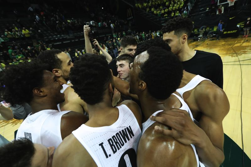 TRIBUNE PHOTO: JAIME VALDEZ - The Oregon Ducks celebrate after defeating the Oregon State Beavers on Saturday night at Matthew Knight Arena.