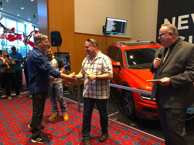 PAMPLIN MEDIA GROUP - Gresham resident William Gustafson, center, is congratulated by Tim Strutz, also of East Multnomah County, on Sunday after Gustafson won a Volkswagen Tiguan at the 2018 Portland International Auto Show. Gustafson and Strutz were among four finalists in the drawing to win the car. At right is Greg Remensperger of Metro Portland New Car Dealers Association.