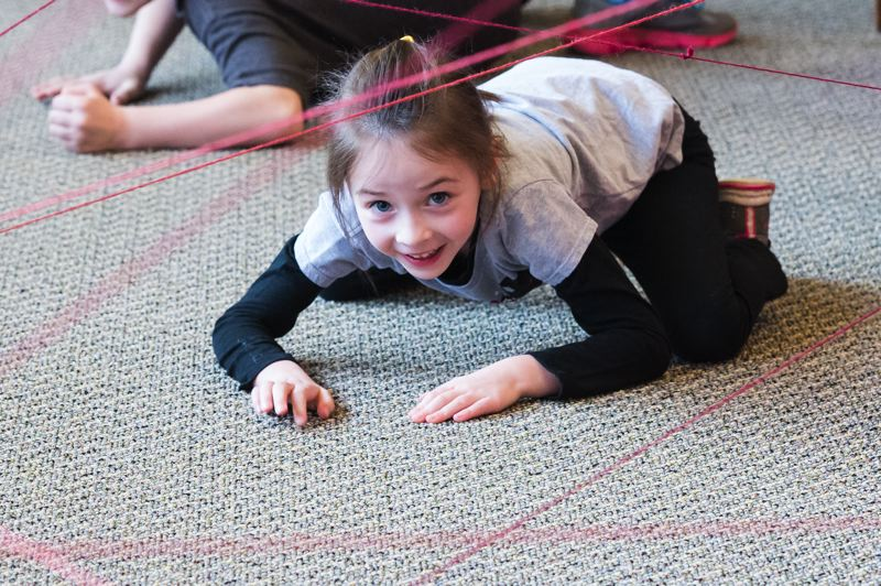 STAFF PHOTO: CHRISTOPHER OERTELL - Elliana Vandehey, 6, from Forest Grove, moves through the Laser Crawl course during the Be a Library Jedi event at the Forest Grove City Library.