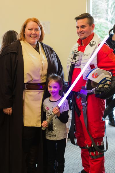 STAFF PHOTO: CHRISTOPHER OERTELL - Jedi Knight Missy Thingelstad and Resistance pilot Jim Moser pose for a photo with Elliana Vandehey, 6, during the Be a Library Jedi event at the Forest Grove City Library.