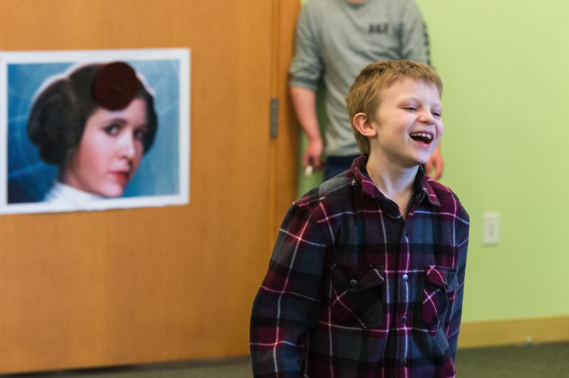 STAFF PHOTO: CHRISTOPHER OERTELL - Alexander Gutierrez, 10, from Forest Grove, plays a game of Pin the Bun on Princess Leia Saturday at the Forest Grove City Library.