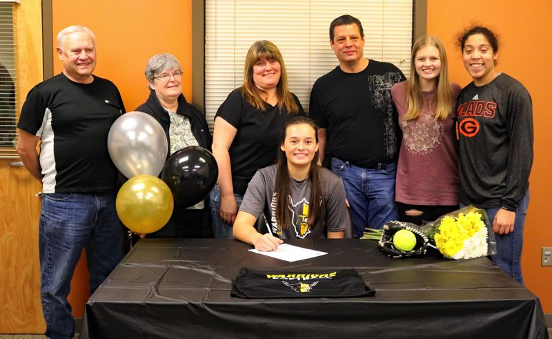 REVIEW/NEWS PHOTO: JIM BESEDA - Gladstone's Shaye Pinner (seated) had the support of family, friends and coaches on Wednesday when she signed a letter of intent to play college softball at Walla Walla Community College.