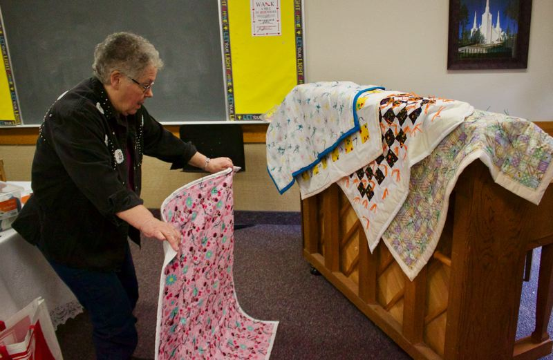 OUTLOOK PHOTO: CHRISTOPHER KEIZUR - Marylou Nordstrom, one of the founding members of the Thursday Morning Quilting Group, lays out some of their work.