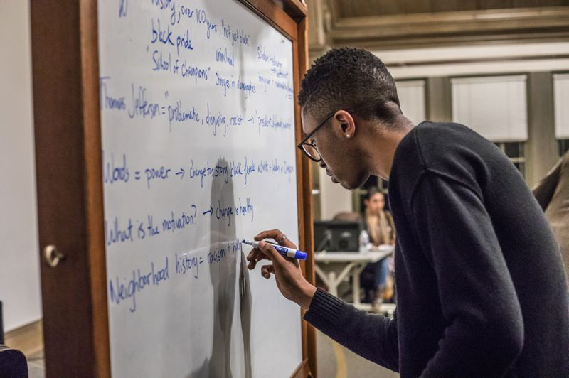 TRIBUNE PHOTO: JONATHAN HOUSE - Tyler White writes down the pros and cons of renaming Jefferson High School during a community meeting on Monday night.