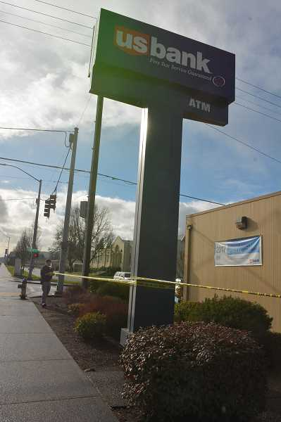 SPOTLIGHT PHOTO: DARRYL SWAN - A Scappoose police officer strings police tape around the perimeter of US Bank in Scappoose following a Tuesday morning robbery. Scappoose Middle School is visible in the distance.