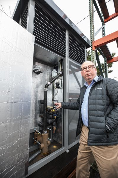 PORTLAND TRIBUNE: JONATHAN HOUSE - Greg Madden shows where the plumbing and elecrical connections are located behind the normally locked rear doors of the Portland Loo.