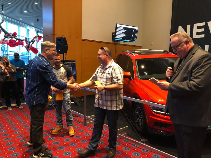 PAMPLIN MEDIA GROUP - Gresham resident William Gustafson, middle, is congratulated by Tim Strutz after Gustafson won a Volkswagen Tiguan at the 2018 Portland International Auto Show. They were among four finalists in a drawing to win the car. At right is Greg Remensperger of Metro Portland New Car Dealers Association.